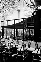 France. Ile-de-france Department. Paris. Bastille place. Tables and chairs covered by snow on the terrace of a cafe restaurant. Winter season. The Place de la Bastille is a square where the Bastille prison stood until the 'Storming of the Bastille' and its subsequent physical destruction between 14 July 1789 and 14 July 1790 during the French Revolution. The square and its surrounding areas are normally called simply Bastille. The July Column (Colonne de Juillet) which commemorates the events of the July Revolution (1830) stands at the center of the square.23.02.05 © 2005 Didier Ruef