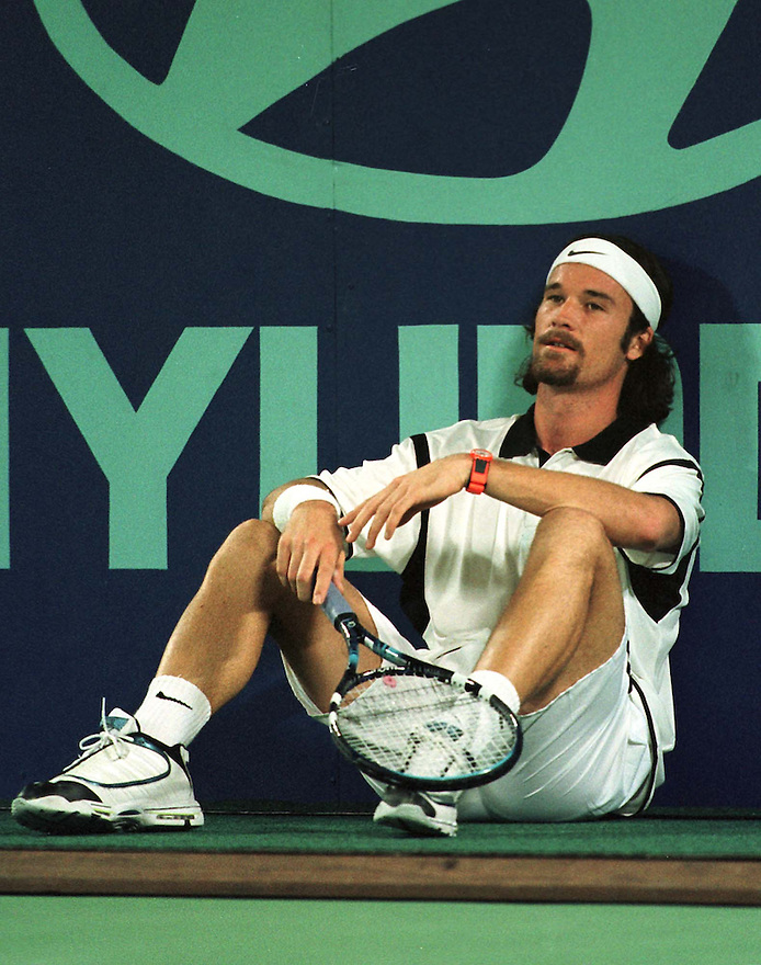 Carlos Moya of Spain slumps against a courtside wall as he waits for French opponent Guillaume Raoux replace a broken shoe lace during their match at the Hopman cup in perth, Monday Jan 4, 1999. Moya defeated Raoux, winning the match 7-6, 2-6, 6-3. (AP Photo/ Jean-Marie Blase)