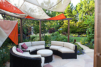 Padded lounge chairs in circle under colorful gazebo on patio in Habets garden, Pleasant Hill, California
