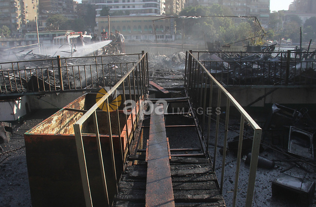 Egyptians try to extinguish the fire after broke out in a restaurant in Kit-Kat distract near Zamalek, January 4, 2015. Giza governor Ali Abd Al- Rahman said that a huge fire erupted in one of the floating restaurants with no injuries and added that the reason of the fire is still under investigation. Photo by Amr Sayed