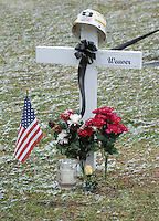A miner's helmet sits atop the cross for Sago miner Jack Weaver at the memorial on the county courthouse lawn in Phillipi, WV Friday, Jan. 6, 2006. Weaver is one of the 12 miners killed in the Sago mine explosion. (Gary Gardiner/EyePush Newsphotos)<br />