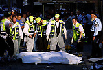 Orthodox Jewish aid workers and policemen stand next to the bodies of the victims after a suspected suicide bomber blew himself up in Jerusalem June 11, 2003. A suspected Palestinian suicide bomber killed at least 16 people and injured more than 60 on a bus, a day after an Israeli assassination attempt against a militant leader. Photo by Quique Kierszenbaum