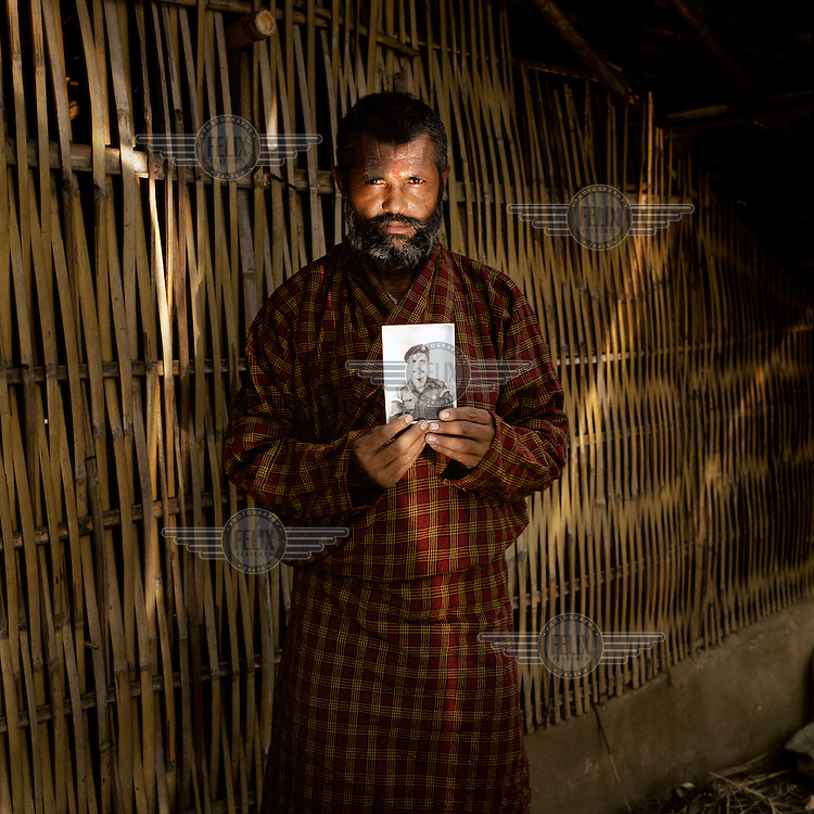 48-year-old Kadhananda Luitel, a Bhutanese refugee, standing in the reflected light from a solar cooker. Kadhananda, who is pictured with the only objects that he took with him upon leaving his homeland, is holding a photograph of himself in his Bhutanese army dress. Like most of the first generation Bhutanese refugees, Kadhananda arrived in Beldangi camp in the early 1990s...