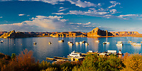 Beautiful, golden sunset light on Lake Powell rocks and Page marina houseboats, under a blue sky with white clouds, at the Arizona and Utah border, USA
