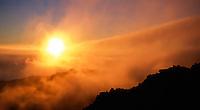 Sunrise through the clouds and over the Hana Highway, seen at 9,745 feet, Haleakala National Park, Maui.