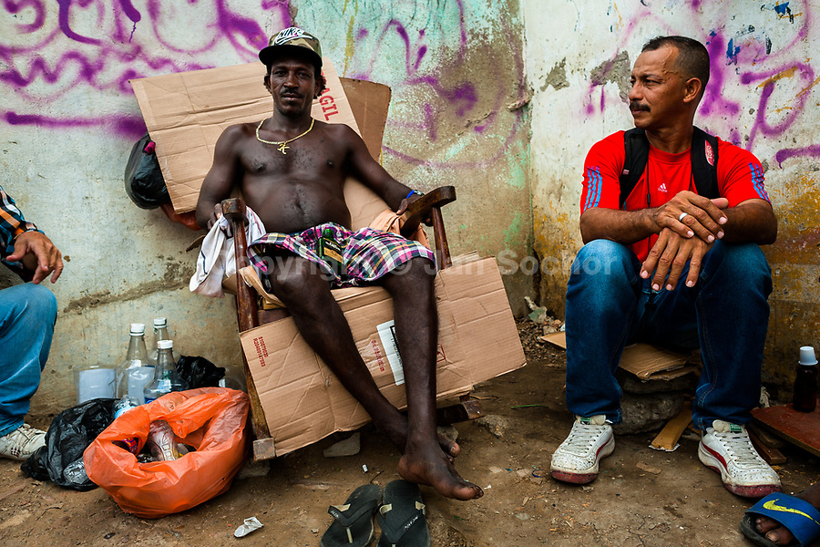 An Afro-Colombian man resells liquor from large bottles in the market of Bazurto in Cartagena, Colombia, 15 April 2018. Far from the touristy places in the walled city, a colorful, vibrant labyrinth of Cartagena's biggest open-air market sprawls to the Caribbean seashore. Here, in the dark and narrow alleys, full of scrappy stalls selling fruit, vegetables and herbs, meat and raw fish, with smelly garbage on the floor and loud reggaeton music in the air, the African roots of Colombia are manifested.