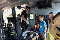 Jake Harris, left, a fireman with the Bentonville Fire Department shows Wyatt Gunderson and his mother Laurie Gunderson how air tanks are attached to seats in a fire truck allowing fireman to suit up with air tanks in a fire truck as they are going to a fire. The Bentonville Fire Department had one of their fire truck at the Bentonville Library during a children's story time to allow kids to look and learn about fire trucks and fireman equipment after being read a story about fire and fireman. Go to nwaonline.com/211008Daily/  to see more photos from around Northwest Arkansas. (NWA Democrat-Gazette/Spencer Tirey)