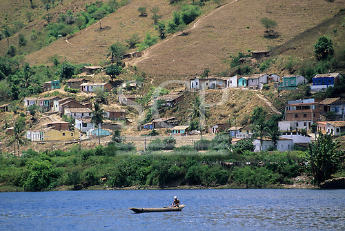 Cachoeira, Bahia, Brazil. A view across the river to the poor area of the village and the fields. A man fishing from his canoe.