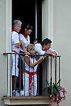 People stand on a balcony as they watch the first bull run of the San Fermin Festival, on July 7, 2013, in Pamplona, northern Spain. The festival is a symbol of Spanish culture that attracts thousands of tourists to watch the bull runs despite heavy condemnation from animal rights groups. (c) PEDRO ARMESTRE