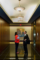 Stock photography of two professionals talking while waiting for the elevator in an attractive office. Models are model released.