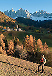 Italy, South Tyrol, Alto Adige, Dolomites, Val di Funes: mountain village St. Magdalena and Le Odle mountains at natural park Puez-Odle, woman with backpack, hiking | Italien, Suedtirol, Dolomiten, Herbststimmung im Villnoesstal, Bergdorf St. Magdalena: mit Dorfkirche, Bauernhoefen vor Geislergruppe, Frau mit Rucksack wandert