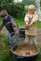 Lehmbackofen im Schulgarten, Garten der Grundschule Nusse wird als Projektarbeit von einer 1. Klasse gestaltet, Kinder mit feuchten Lehm für den Bau eines Lehmbackofens, Gartenarbeit