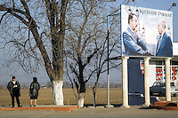 Azerbaijan. Ganja region. Ganja. A couple (man and woman) stand on the sidewalk of a concrete road. A huge poster shows the current President of Azerbaijan, Ilham  Aliyev (born December 24, 1961) and his father Heydar Aliyev, the deceased political leader. Ilham  Aliyev also functions as the head of the New Azerbaijan Party. Heydar Aliyev ( May 10, 1923 - December 12, 2003), also spelled as Heidar Aliev, Geidar Aliev, Haydar Aliyev, was the president of Azerbaijan for the New Azerbaijan Party from June 1993 to October 2003. On the publicity, Ilham and Heydar Aliyev are standing near oil derricks on the Caspian sea. © 2007 Didier Ruef