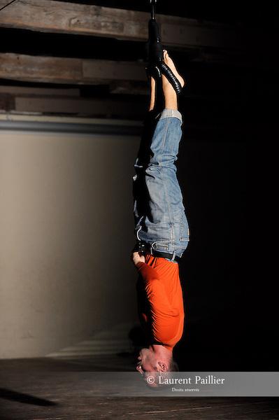LA 36E CHAMBRE....Choregraphie : Kevin Jean..Avec :..Kevin Jean..Cadre : Des solis et des lieux..Lieu : Fondation Royaumont..Ville : Asniere sur Oise..Le : 07 09 2011..© Laurent PAILLIER / photosdedanse.com..All rights reserved....Les pieds dans des garrots de pendaison, Kevin Jean part du sol puis se suspend au bout d'une corde, tête en bas, avec pour contrepoids un bidon. A partir de cette posture, il offre d'étonnantes variations qui évoquent tour à tour la chute, l'étrangeté d'un corps «en mauvaise posture», entravé et pourtant encore libre de ses mouvements (observant à droite et à gauche, dans la posture tranquille des mains dans les poches, éprouvant des torsions du dos). Kevin Jean joue ainsi du corps empêché et comme échoué, à la manière d'un corps étranger qu'il faudrait reconquérir et escalader. Parfois on entend les grincements de la corde, parfois non, ce qui ajoute une tension particulière.