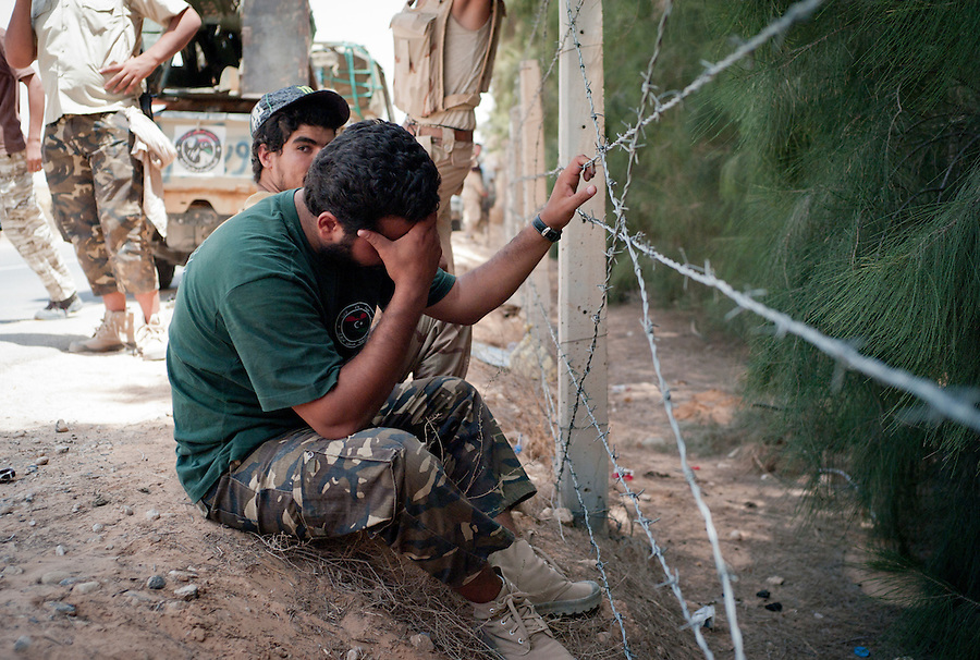 Rebel fighters rest on the side of the road leading to Zawiya near Bir Ayad, Libya.