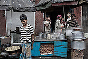 Pedestrians and street side dwellers stop for tea on the streets of Kolkata in West Bengal, India.