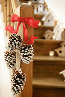 Decorated pine cones tied with ribbon hang from the banister of the wooden staircase