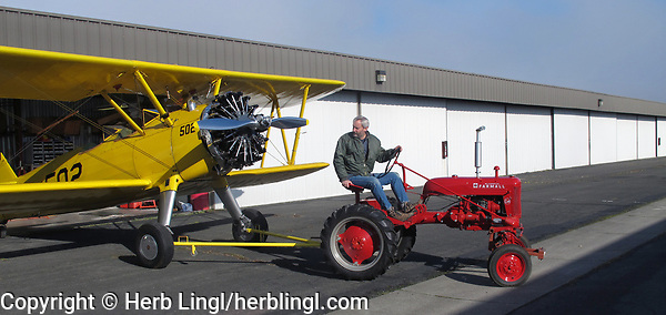Pilot and aircraft mechanic Bryan Turner tows his Stearman from his hangar with his Farmall Tractor at the Petaluma Municipal Airport, Petaluma, Sonoma County, California.