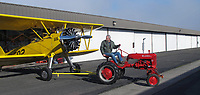 Pilot and aircraft mechanic Bryan Turner tows his Stearman from his hangar with his Farmall Tractor at the Petaluma Municipal Airport, Petaluma, Sonoma County, California.