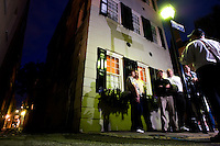 A group of tourists take a night time ghost tour of Charleston, SC.