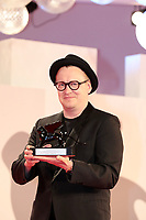 """VENICE, ITALY - SEPTEMBER 11: Teemu Nikki poses with the Audience Award Armany Beauty for """"The Blind Man Who Did Not Want To See Titanic"""" at the awards winner photocall during the 78th Venice International Film Festival on September 11, 2021 in Venice, Italy."""