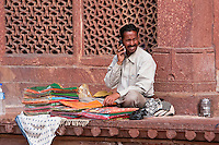 Fatehpur Sikri, Uttar Pradesh, India.  Fabric Vendor Using Cell Phone.  Visitors to the tomb of Sheikh Salim Chishti leave offerings of fabric on his grave.