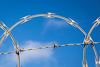 Barbed wire and razor wire at the top of a fence with blue sky and wisps of cloud for background.