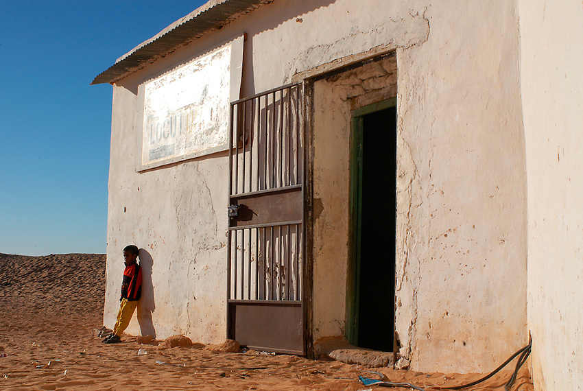A boy waits outside a locutory in Aaiun wilaya on December 14, 2003, in the Saharawi refugee camps. Saharawi people have been living at the refugee camps of the Algerian desert named Hamada, or desert of the deserts, for more than 30 years now. Saharawi people have suffered the consecuences of European colonialism and the war against occupation by Moroccan forces. Polisario and Moroccan Army are in conflict since 1975 when Hassan II, Moroccan King in 1975, sent more than 250.000 civilians and soldiers to colonize the Western Sahara when Spain left the country. Since 1991 they are in a peace process without any outcome so far. (Ander Gillenea / Bostok Photo)