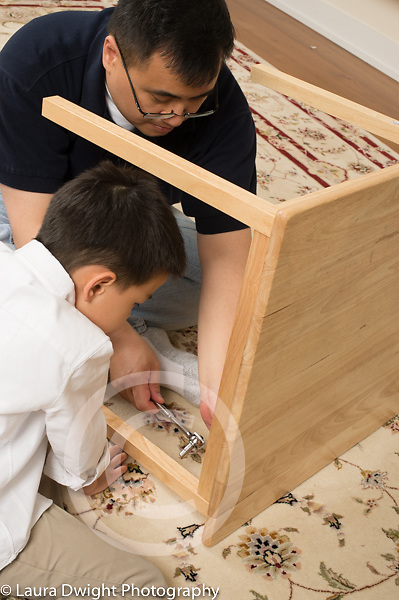 Father repairing table, 6 year old son looking on and learning how to use tools