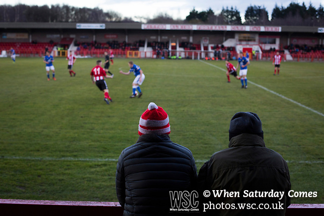 Witton Albion 1 Warrington Town 2, 26/12/2017. Wincham Park, Northern Premier League. Two spectators watching the action at Wincham Park, home of Witton Albion (in red) during their Northern Premier League premier division fixture with Warrington Town. Formed in 1887, the home team have played at their current ground since 1989 having relocated from the Central Ground in Northwich. With both team chasing play-off spots, the visitors emerged with a 2-1 victory, the winner being scored by Tony Gray in second half injury time, watched by a crowd of 503. Photo by Colin McPherson.