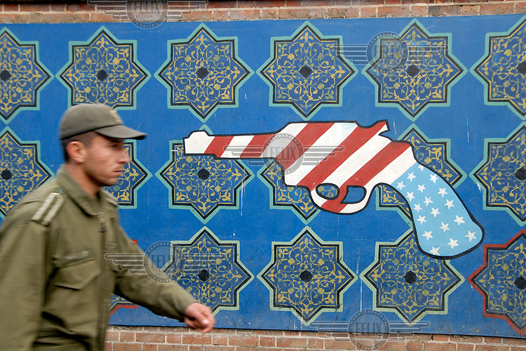 A soldier passes a propaganda mural on a wall of the former US embassy, representing a gun in the colours of the American flag.