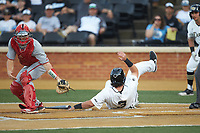 Bobby Seymour (3) of the Wake Forest Demon Deacons slides across home plate as North Carolina State Wolfpack catcher Patrick Bailey (5) waits for the throw at David F. Couch Ballpark on April 18, 2019 in  Winston-Salem, North Carolina. The Demon Deacons defeated the Wolfpack 7-3. (Brian Westerholt/Four Seam Images)