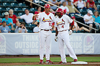 Daryl Jones (4) of the Springfield Cardinals talks with Cardinals manager Ron Warner (57) while standing on third base during a game against the Midland RockHounds at Hammons Field on July 11, 2011 in Springfield, Missouri. (David Welker / Four Seam Images)