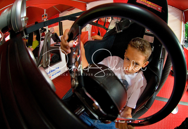 A young NASCAR fan (no model release) tries his hand in a stock car simulator. ..For several days leading up to the May races at the Lowe's Motor Speedway, uptown Charlotte streets are transformed into a showcase of motor sports and non-stop entertainment. ..Photo taken in 2007. Photographer also has images from 2008.