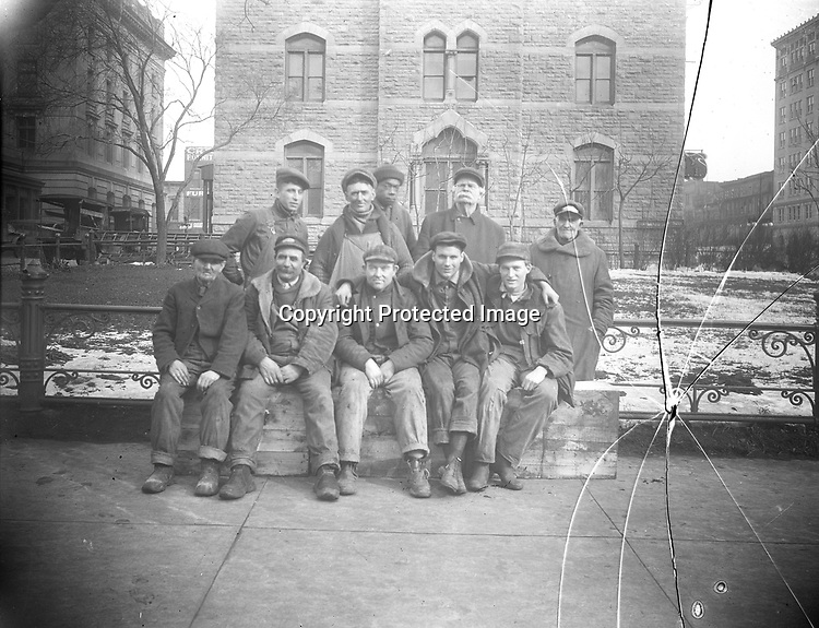 Work Crew in Front of Courthouse<br /> Glass negatives are understandably prone to breakage. The most severely shattered are lost, but ones with less severe breakage can be pieced together on a scanner bed.<br /> <br /> A cadre of workers hams it up in this wintertime scene in front of Lincoln's old Courthouse and Post Office, which was built in the 1870's. Photographer John Johnson peeks out back center, indicating that someone, possibly an assistant, snapped the shutter. Johnson's primary job was as a janitor at the new U. S. Courthouse and Post Office north (left) of the old building.  That photography was more than a hobby to Johnson is suggested both by the quality of his photographs and by the quantity of his images discovered so far—approximately 500 glass plate negatives have been found in various collections.