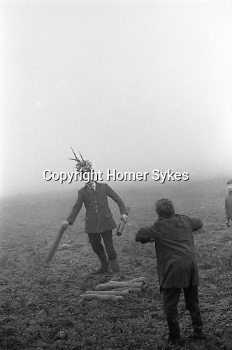 The Haxey Hood Game,<br /> Haxey, Humberside 6 January 1971<br /> <br /> <br /> The Chief Boggin Arthur Clark throws up one of the twelve childrens sack cloth hoods in Upper Thorpe Field on the boundary of Westwoodside and Haxey (the Hoodlands field no longer exists). There twelve sack hoods are thrown up. These are known as children's hoods since twenty pence is given to any boy or girl who gets one to either of the two pubs in Haxey, or to the Carpenter's Arms in Westwoodside, without being stopped by a Boggin. If he is stopped, the hood goes back to the start to be thrown up again.<br /> <br /> At about four o'clock a leather hood is thrown up, and a scrum known as the 'sway' forms round it. The teams of men, who can come from anywhere, push against each other trying to get the hood to their favourite pub. Usually several hours pass before the hood reaches a goal, and when it does drinks are on the house. The hood stays in the pub until the following New Year's Eve when it is redeemed by the boggin the pubs in the area to drum up interest in the game.