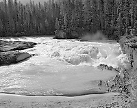"""""""Natural Bridge Over the Kicking Horse River"""" <br /> Yoho National Park; British Columbia, Canada<br /> <br /> This photo shows the powerful force of moving water. The considerable volume of the Kicking Horse River cut a large hole through rock but left a ledge above the hole as a natural bridge over the river. The photograph shows the ferocious descent of whitewater into the hole and the flat ledge above it (on the right) as well as a path across the river. I exposed two black and white films to be certain that I captured the wall of water in the foreground as it pushed toward the bank. While I admired the power of water, I believed that I could feel spirits of early people who crossed the river on this bridge for many hundreds of years."""