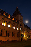 The Neo-gothic building of the Oxford Natural History Museum at dusk under a full moon.