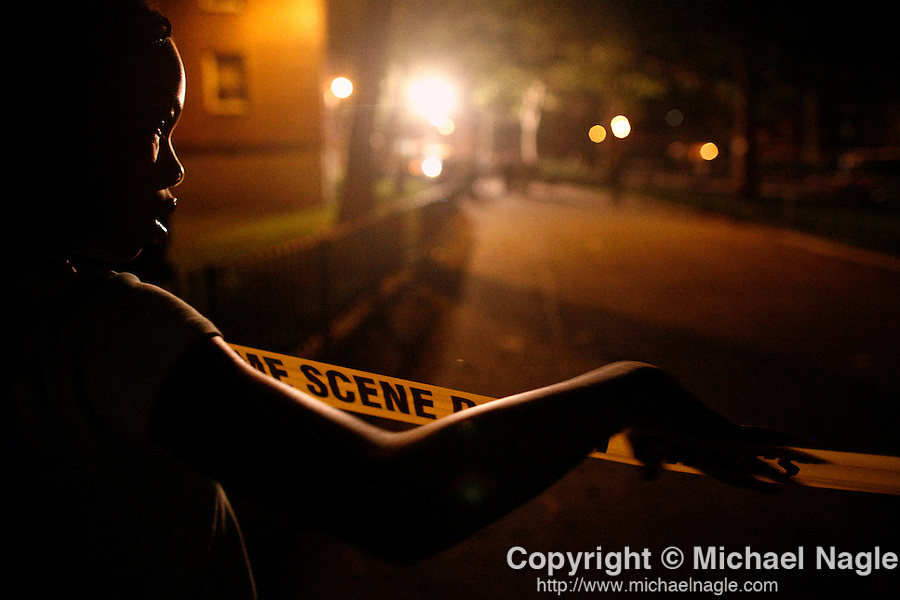 NEW YORK -- JULY 24, 2006:  A young girl watches the scene at the Glenwood Houses where NYPD detectives investigate a police involved shooting that interrupted a BBQ on July 24, 2006 in Brooklyn.  (PHOTOGRAPH BY MICHAEL NAGLE)