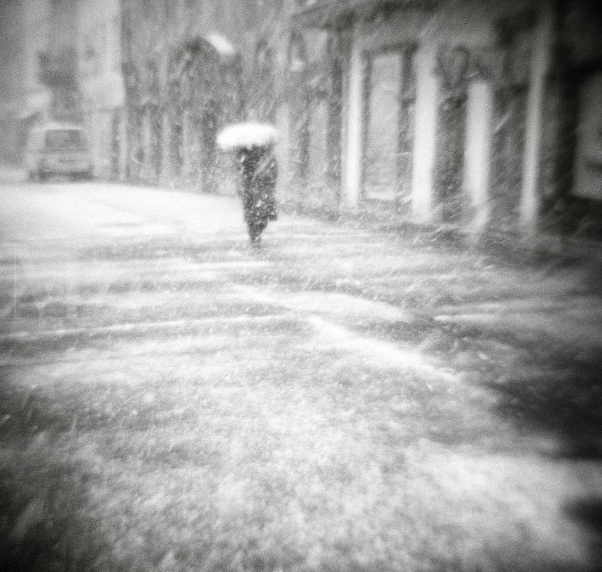 Snow gathers on an umbrella during an urban snowstorm.