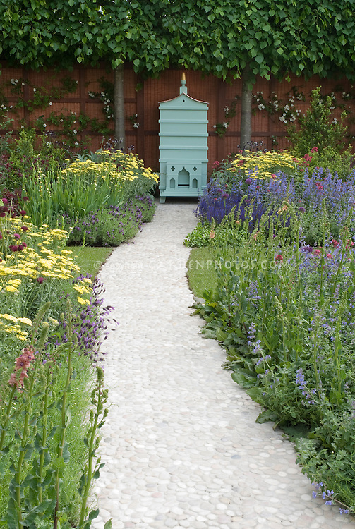 Beehive integrated into beautiful garden with white stone pathway leading to garden fence wall, flowers of Achillea, Nepeta, Verbascum and other flowering perennials in bloom
