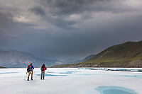 Hikers travel the aufies on the Marsh Fork of the Canning River. the river comprises the western border of the Arctic National Wildlife Refuge in the Brooks Range mountains, Alaska.