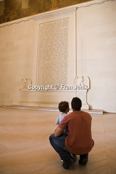 An african-american man holds his young son in his arms as he reads President Abraham Lincoln's Emancipation Proclamation at the Lincoln Memorial in Washington D.C.