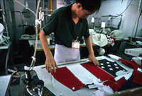 A garment worker irons T-shirts styled as American flags at the Wiseform Clothing Factory in Shenzhen, China..06-SEP-01