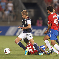 USMNT midfielder Stuart Holden (11) dribbles through defenders. In CONCACAF Gold Cup Group Stage, the U.S. Men's National Team (USMNT) (blue/white) defeated Costa Rica (red/blue), 1-0, at Rentschler Field, East Hartford, CT on July 16, 2013.