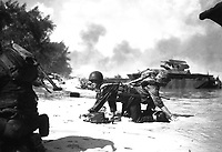 It appears that one Marine is relieving another on the beach at Saipan but they are really crawling under enemy fire, to their assigned positions.  June 1944.  Sgt. James Burns.  (Marine Corps)<br /> Exact Date Shot Unknown<br /> NARA FILE #:  127-GR-113-83260<br /> WAR & CONFLICT BOOK #:  1174