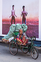 A women and her belongings in a cart in the street of Phnom Penh, behind her a Photo Mural, Cambodia