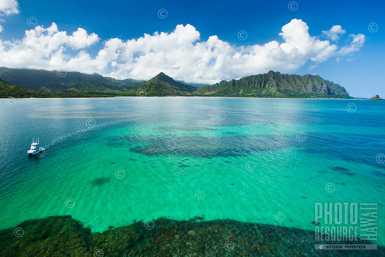 An aerial perspective of a boat sailing past a sandy area of reef past the Kane'ohe Sandbar, with Kualoa Valley and Chinaman's Hat in the background on O'ahu.