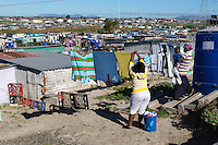 South Africa, Cape Town, Khayelitsha Township.  Woman Hanging her Laundry.  Note the blue outdoor portable toilets.