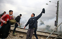 Pictured: A group of refugees with tear gas in the background move back after some of them threw stones and batter down the barbed wire gate of the fence Monday 29 February 2016<br /> Re: A crowd of migrants has burst through a barbed-wire fence on the FYRO Macedonia-Greece border using a steel pole as a battering ram.<br /> TV footage showed migrants pushing against the fence at Idomeni, ripping away barbed wire, as FYRO Macedonian police let off tear gas to force them away.<br /> A section of fence was smashed open with the battering ram. It is not clear how many migrants got through.<br /> Many of those trying to reach northern Europe are Syrian and Iraqi refugees.<br /> About 6,500 people are stuck on the Greek side of the border, as FYRO Macedonia is letting very few in. Many have been camping in squalid conditions for a week or more, with little food or medical help.
